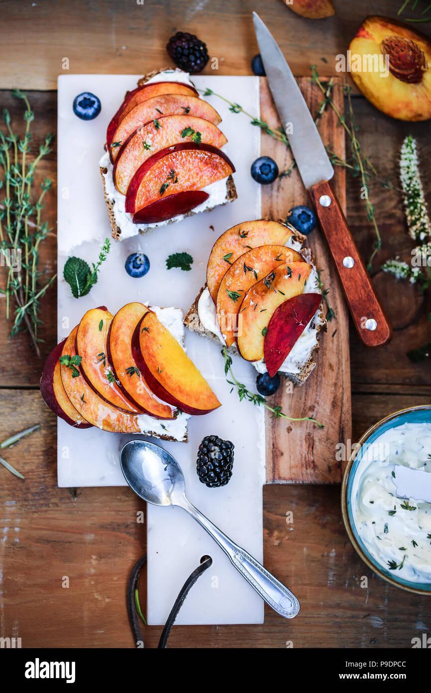 Hierbas frescas, queso de cabra y mousse de melocotones crostini. Imagen De Stock