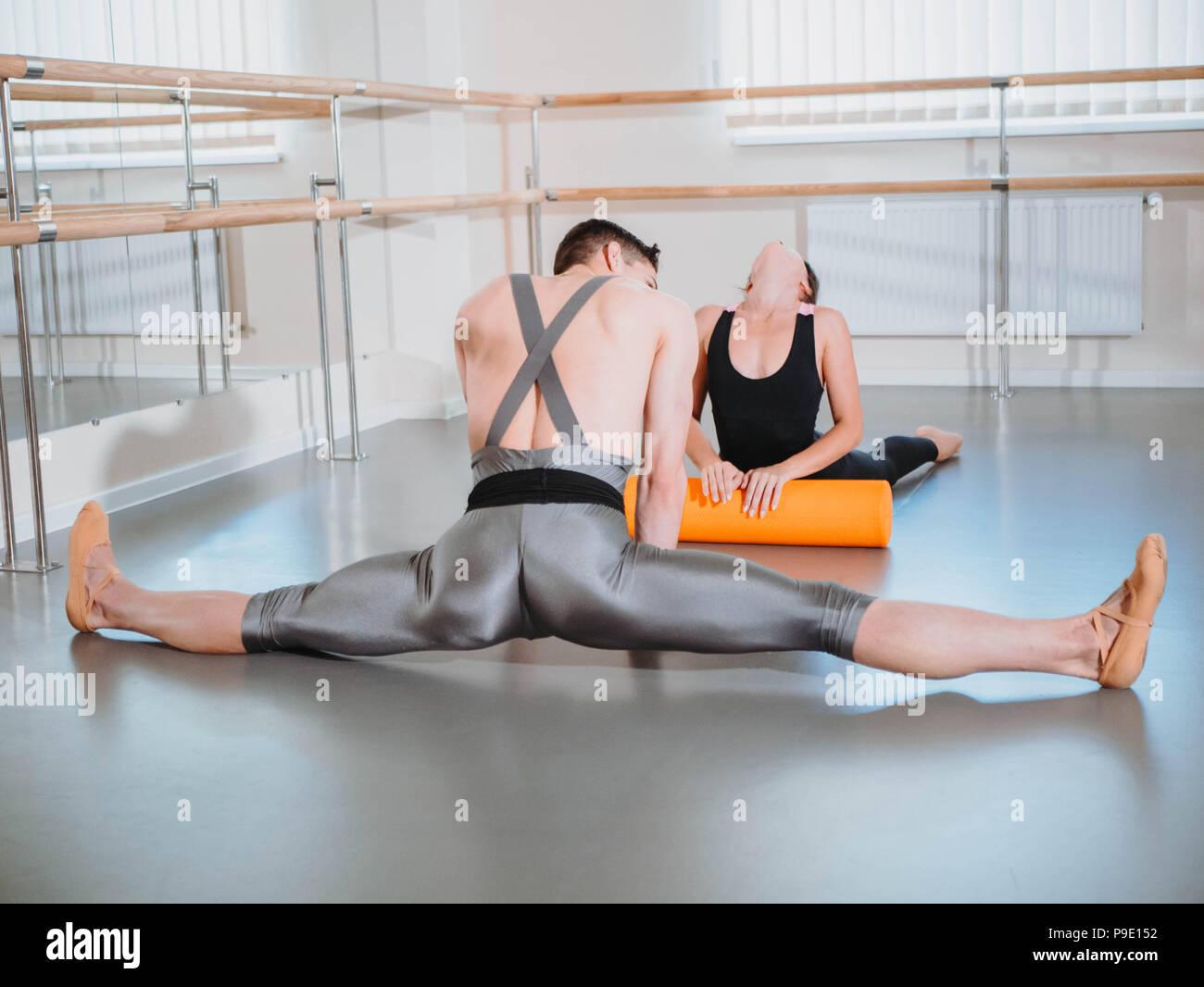 Preparación del cuerpo antes de que el rendimiento en el estudio de ballet. Bailarín y bailarina calentando cerca de barre en el ensayo. Imagen De Stock