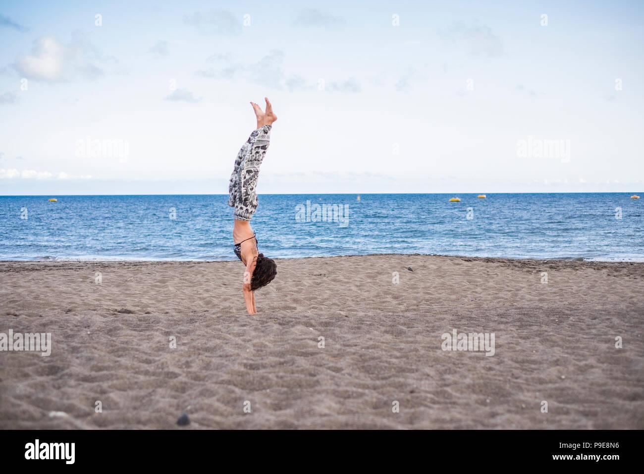Bastante agradable chica caucásica de pie sobre la mano que está en la playa, en la actividad de ocio al aire libre en verano. El océano en el backgorund. disfrutando de la vida y el equilibrio Imagen De Stock