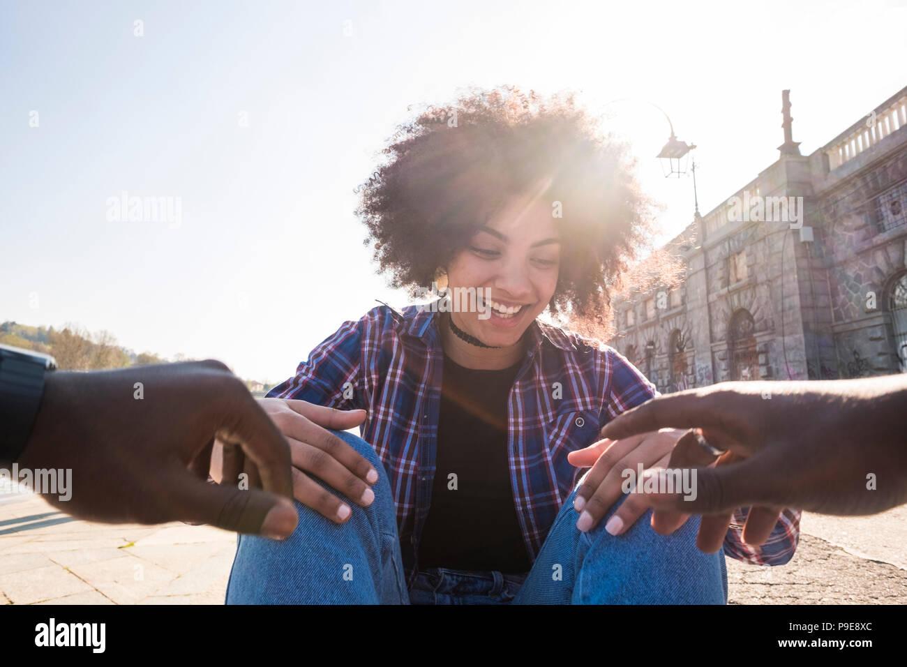 Hermosa raza negra bonito cabello étnico gyoung girl divertirse con un hombre africano sonriendo y riendo con él. la gente feliz en la ciudad. retroiluminación y s Imagen De Stock