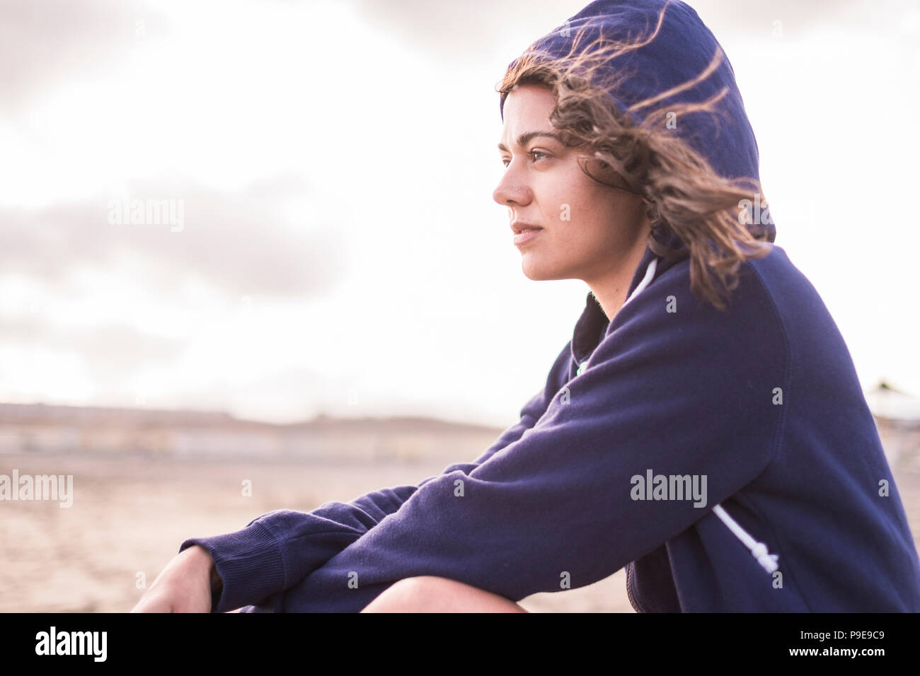Hermosa chica sentada en la playa al aire libre en vacaciones de verano. perdido en sus pensamientos con la independencia y la libertad concepto. brillante cielo con nubes en Imagen De Stock
