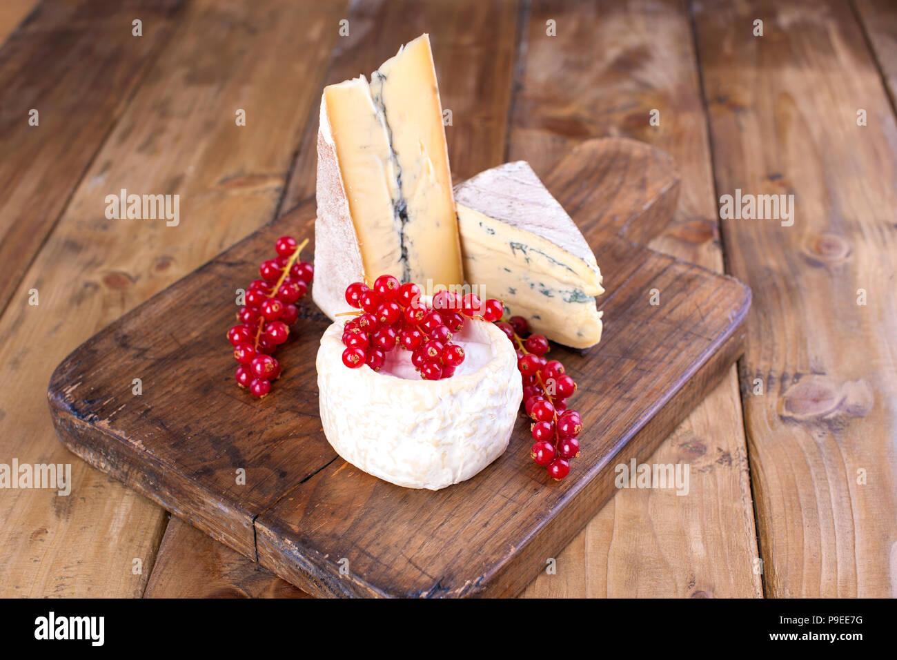 Distintos quesos con moho blanco y azul. Las bayas de grosellas rojas flores blancas. Fondo de madera y espacio libre para el texto o publicidad Imagen De Stock