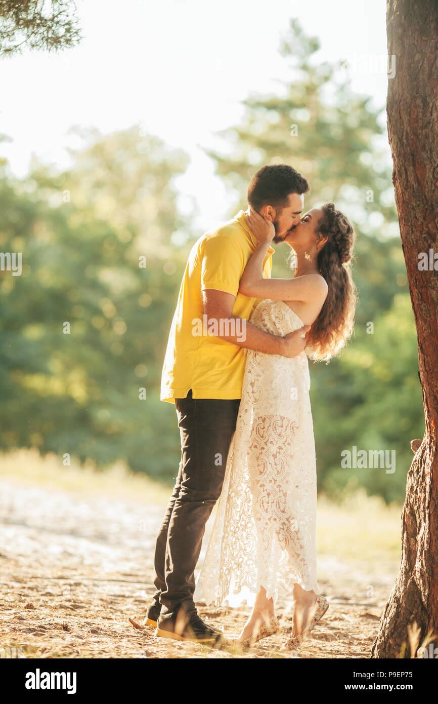 Joven Pareja Enamorada Besos En Bosque Contra El Fondo Del árbol