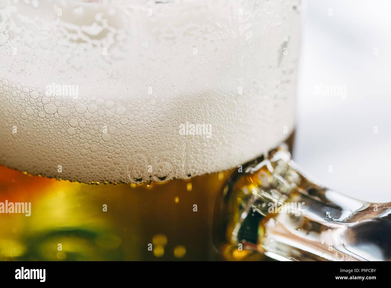 Cerca de un vaso de medio litro de cerveza con espuma espumosa en la parte superior. Foto de stock