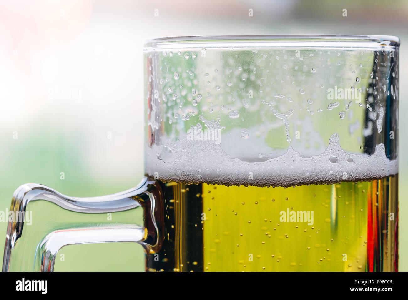 Primer plano de un vaso de cerveza con espuma en la parte superior. Foto de stock