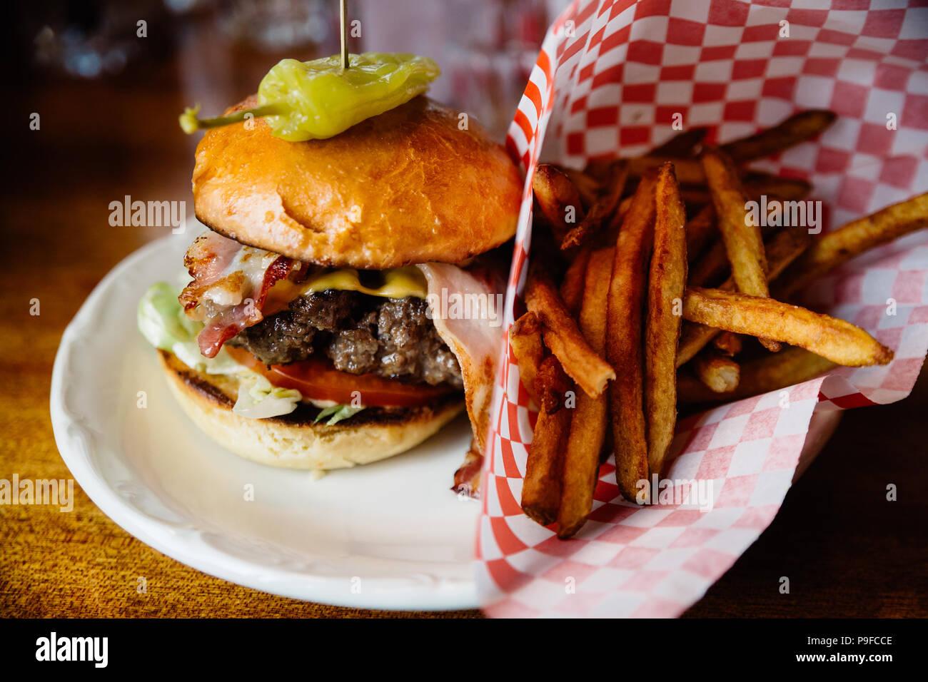 Hamburguesa con tocino, queso y pimienta jalapeño y papas fritas en el lateral. Foto de stock