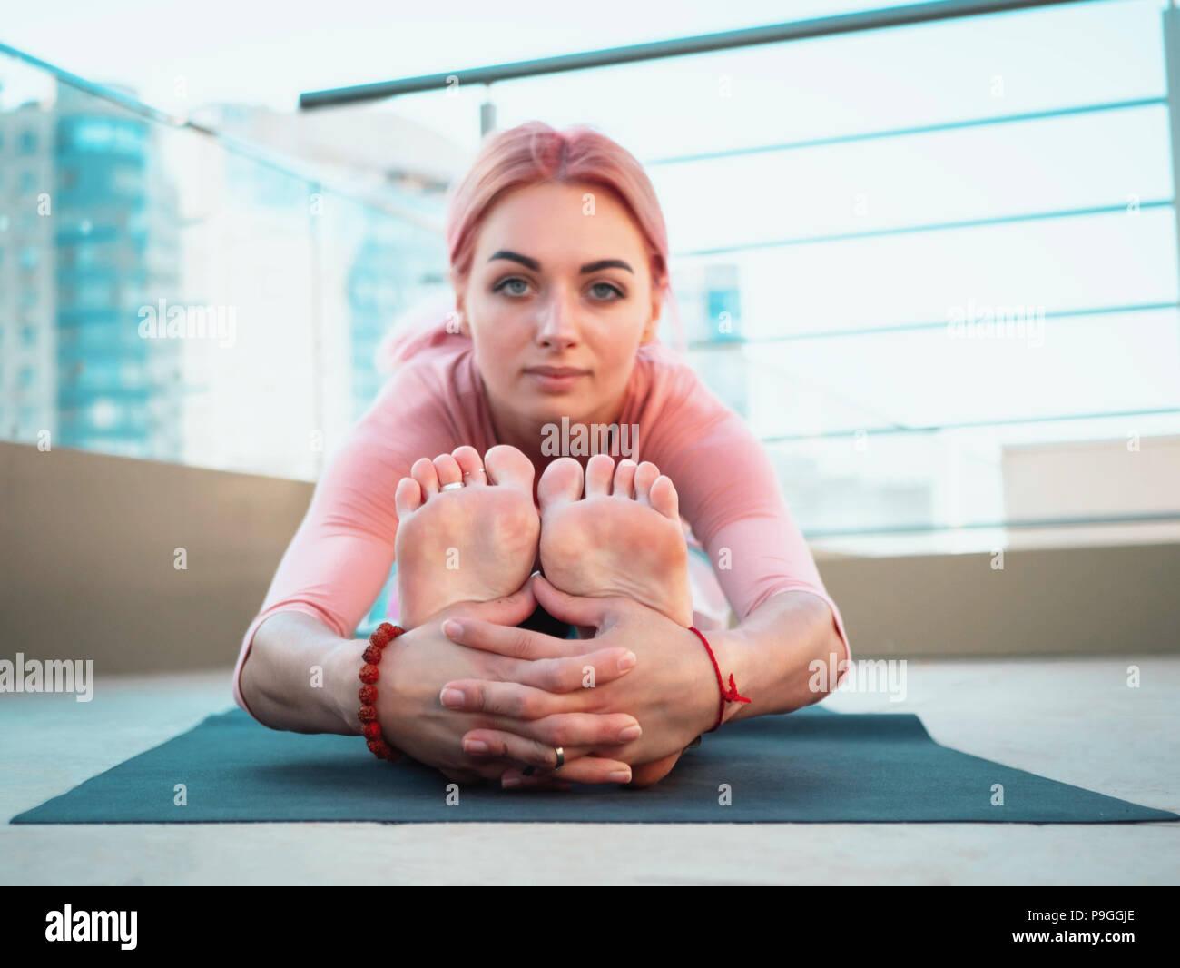 Joven mujer delgada de color rosa con el cabello teñido haciendo la práctica del yoga en la terraza de la ciudad moderna. Chica mantenerse en forma y cuerpo sano relajante en la azotea durante la práctica plantean Imagen De Stock