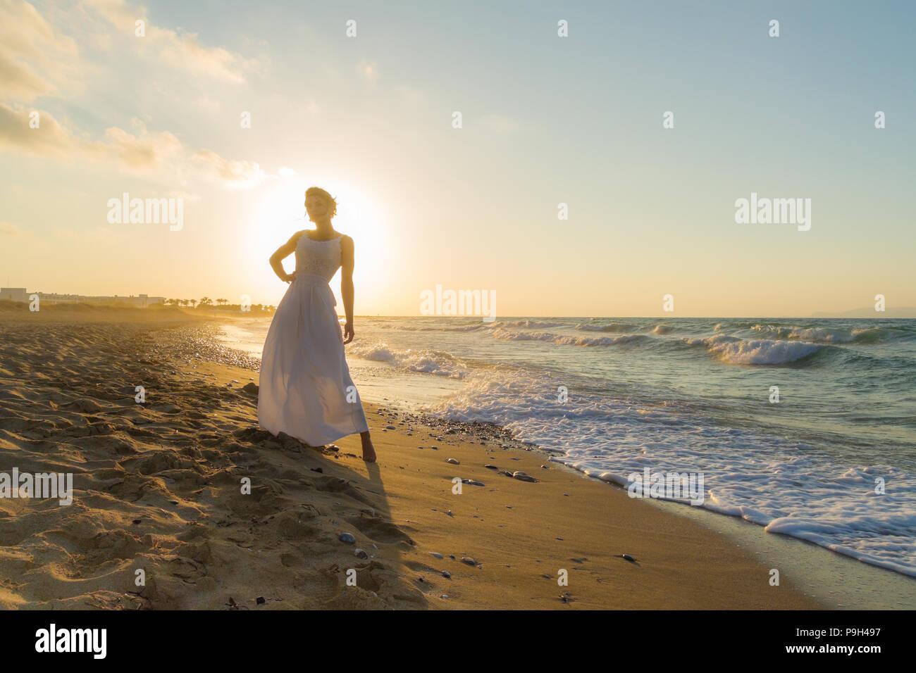 Mujer en vestido blanco, descalzo, sentirse feliz, vivo y libre en la naturaleza meditando en sandy Misty Beach respirar aire fresco del océano limpio al anochecer. Vacaciones de verano concepto de estilo de vida Imagen De Stock