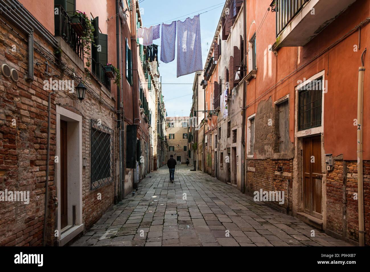 Un hombre que camina sobre una calle casi vacía en el secado de la ropa de cama en Venecia, Italia Foto de stock