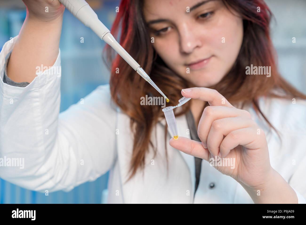 Mujer con multipipette Técnico en laboratorio genético de investigación de PCR. Chica estudiante use pipeta Foto de stock