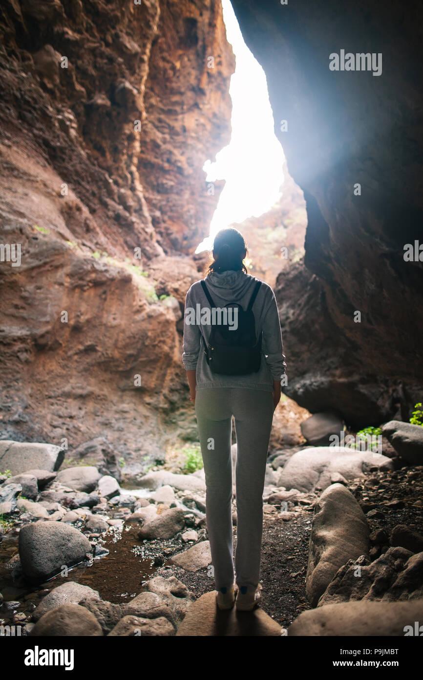 Silueta de la mujer del viajero en la cueva de la montaña. Luz al final de la cueva Imagen De Stock