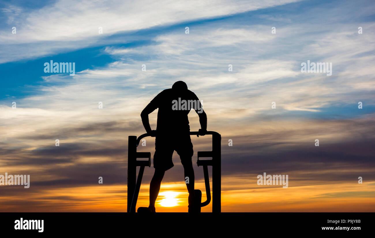 Vista trasera del hombre mediante máquina de ejercicio en las calles de la ciudad al amanecer. Imagen De Stock