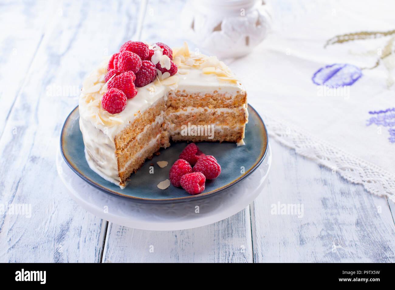 Cortar el pastel con crema blanca, para el desayuno. Una fruta de mango. Fondo blanco, con mantel de encaje y espacio libre para el texto o publicidad Imagen De Stock