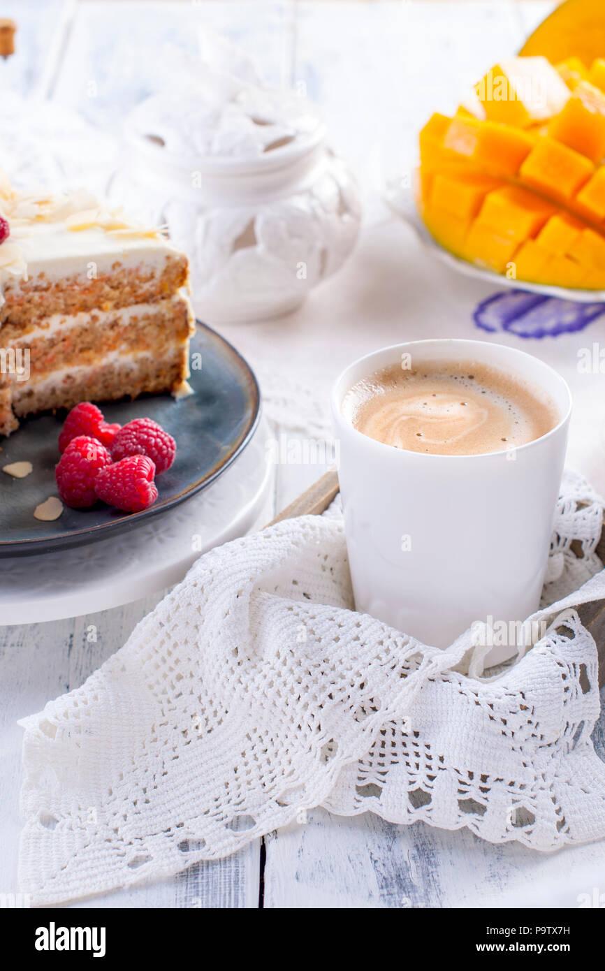 Cortar el pastel con crema blanca, para el desayuno. Una fruta de mango. Fondo blanco, manteles con encajes, una taza de café y espacio libre para el texto o publicidad Imagen De Stock