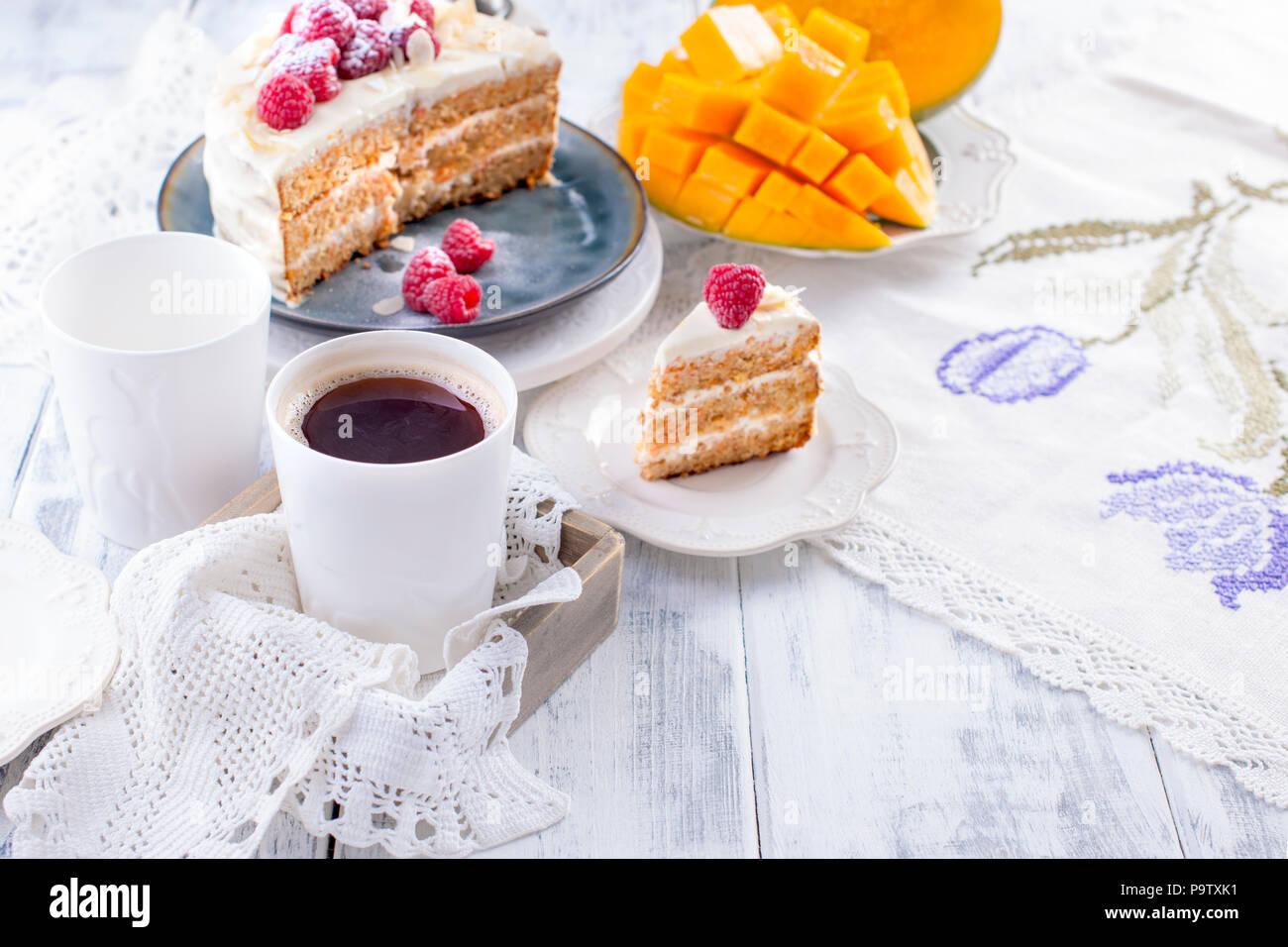 Cortar el pastel con crema blanca, para el desayuno. Una fruta de mango. Fondo blanco, manteles con encajes, una taza de café y espacio libre para texto o publicidad. Imagen De Stock