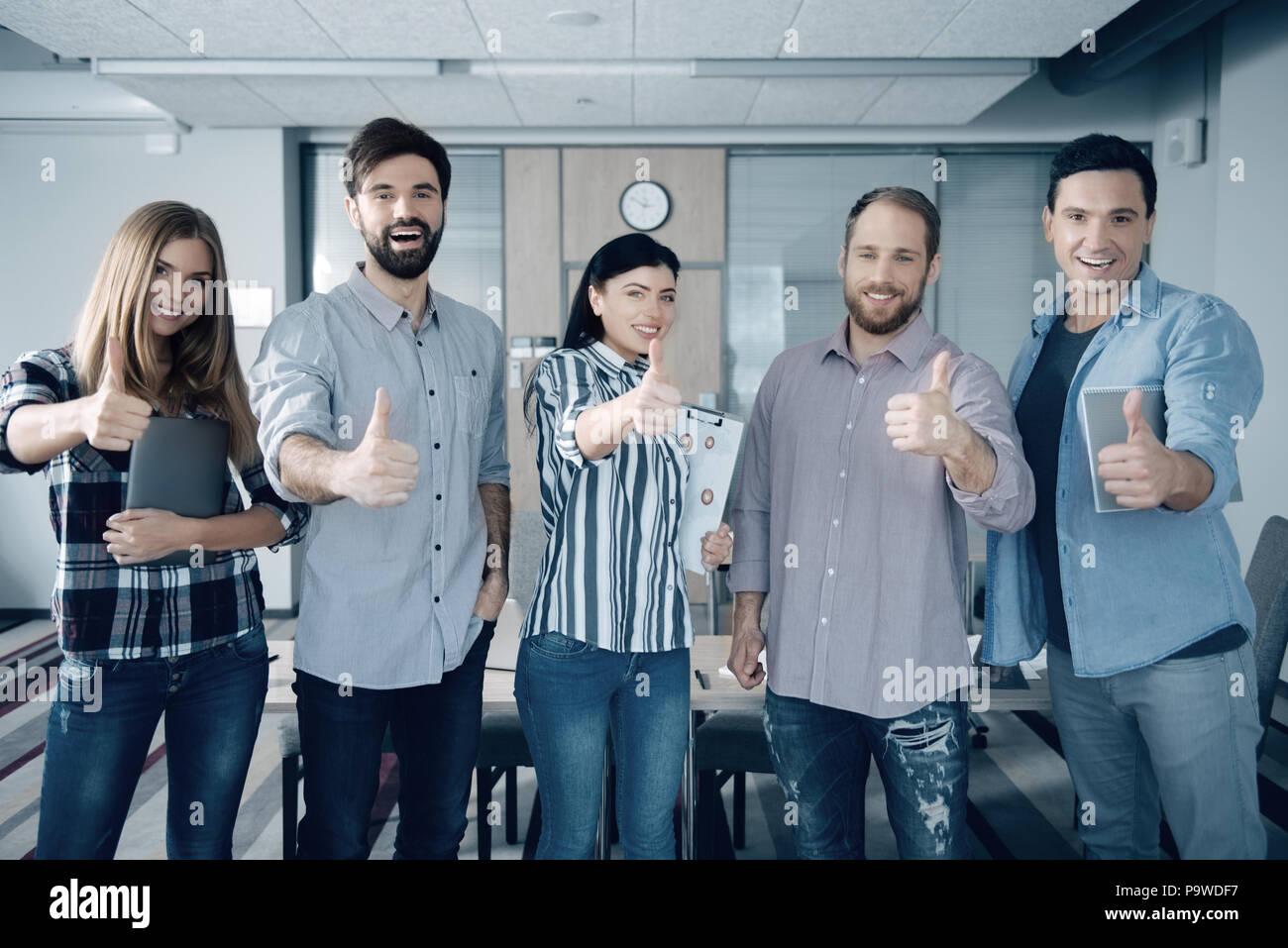 Disfrute cada día. Grupo de jóvenes colegas thumbing alegre y ponerse de pie en la oficina Imagen De Stock