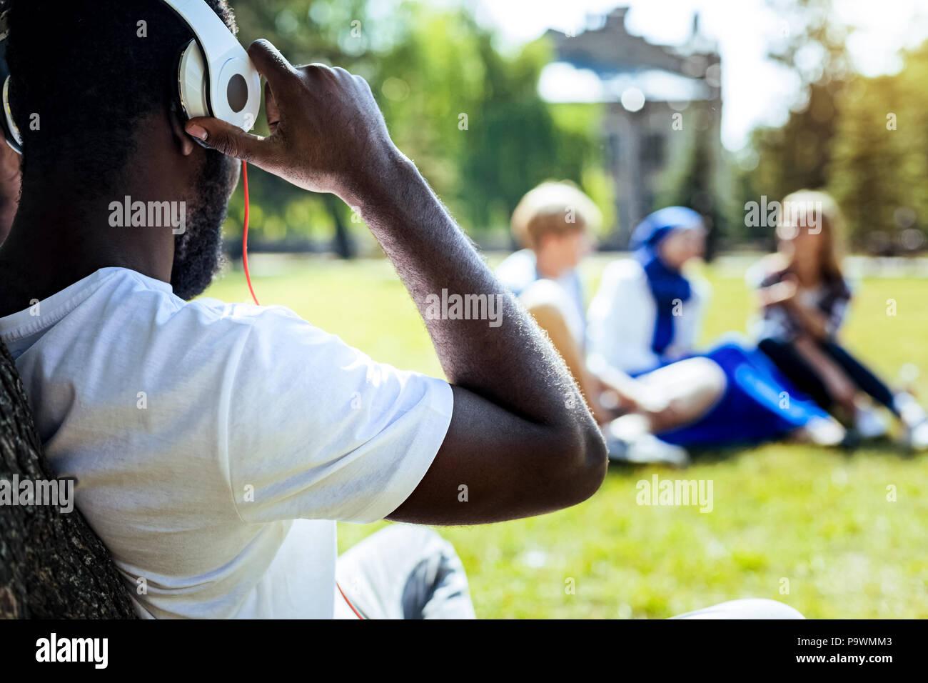 Caballero americano africano disfruta de la música en el parque Imagen De Stock