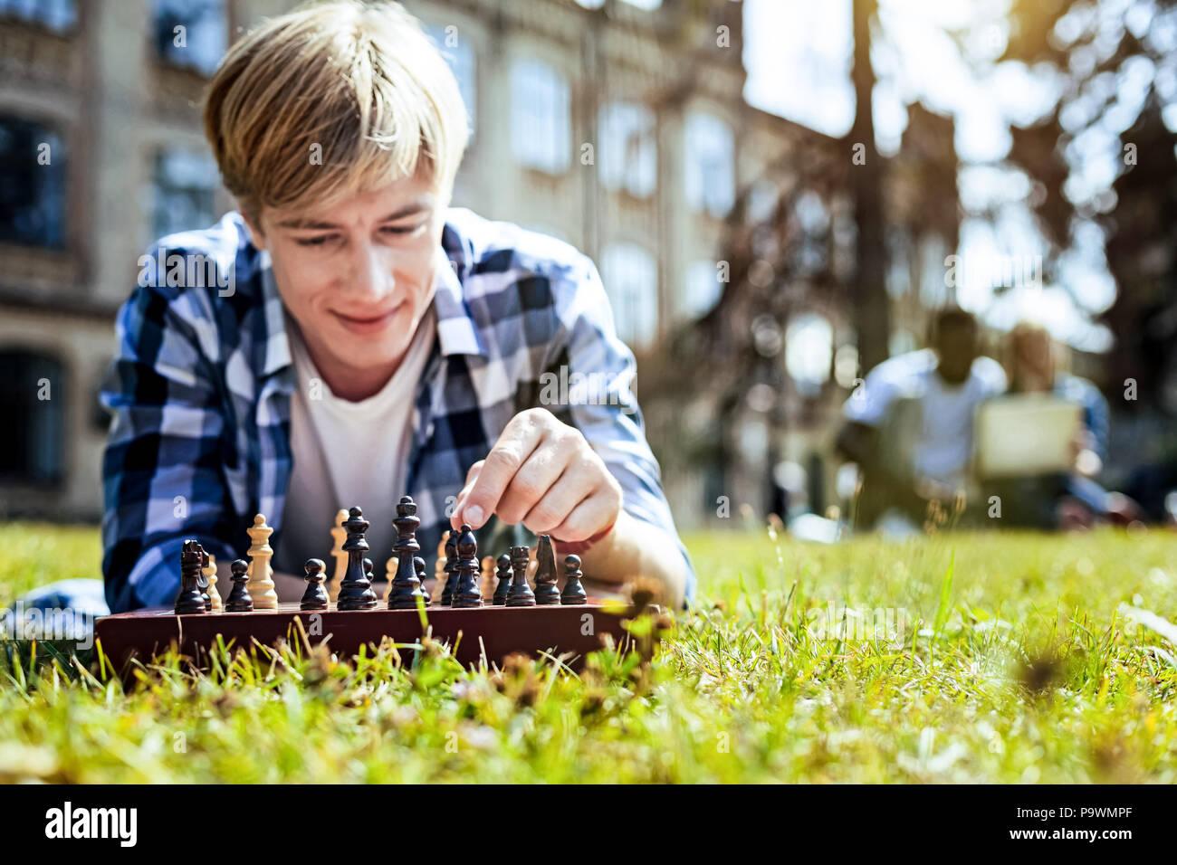Chico sonriente disfrutando de un juego de ajedrez al aire libre Imagen De Stock