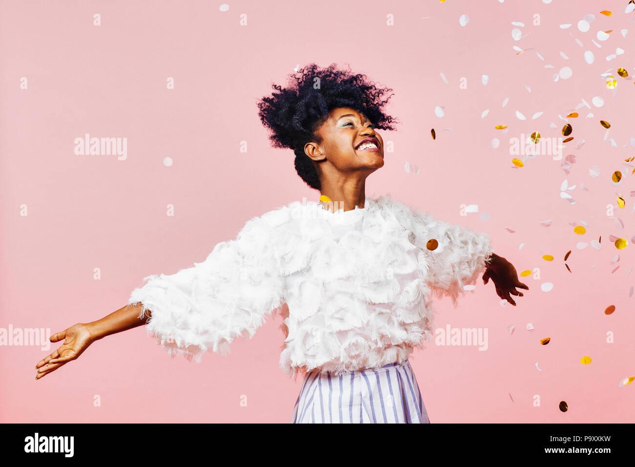 Un momento mágico - Retrato de una chica muy alegre con los brazos, sonriendo confeti cayendo Imagen De Stock