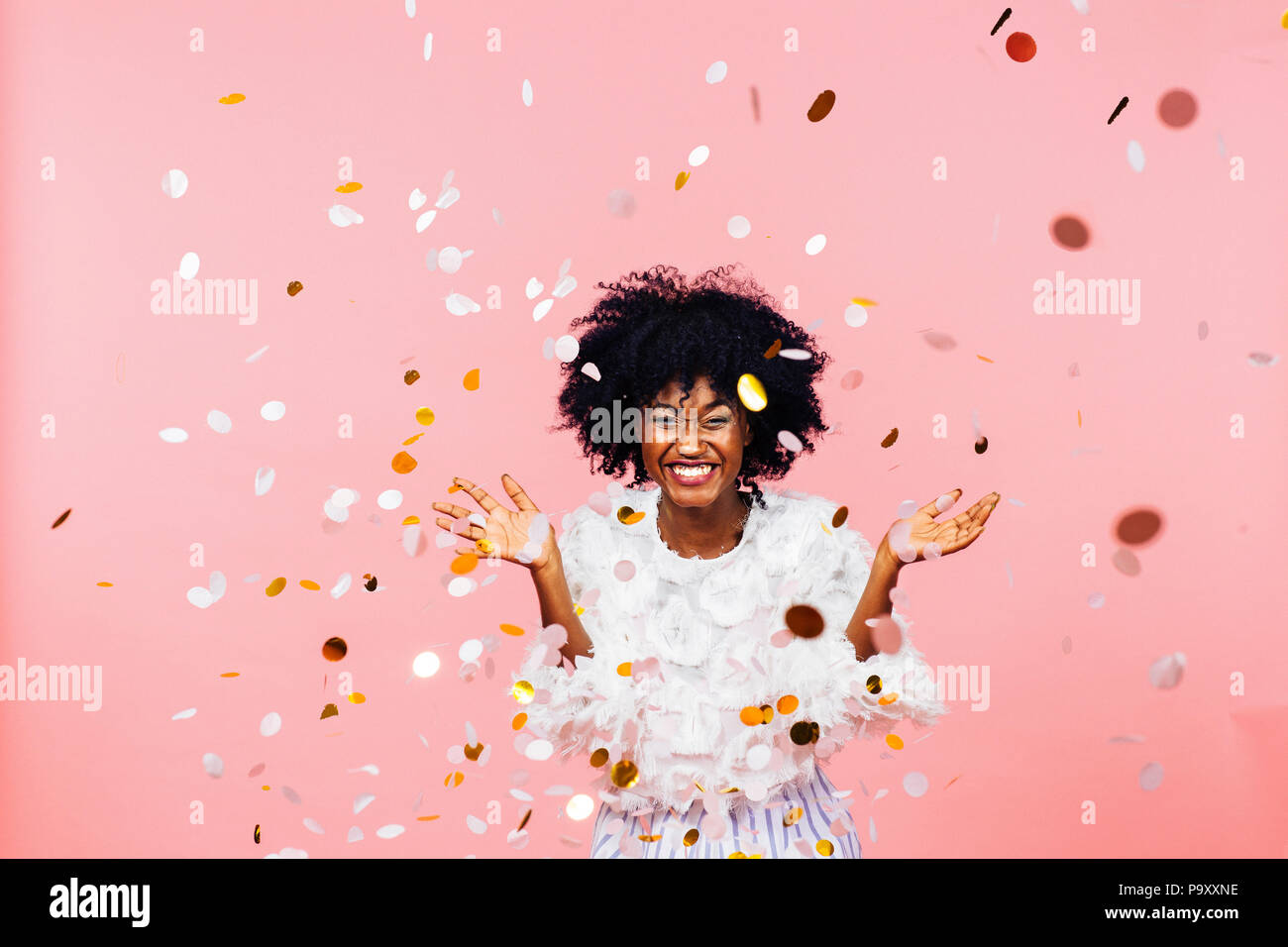 Celebrando la felicidad, mujer joven con gran sonrisa lanzando confeti Imagen De Stock