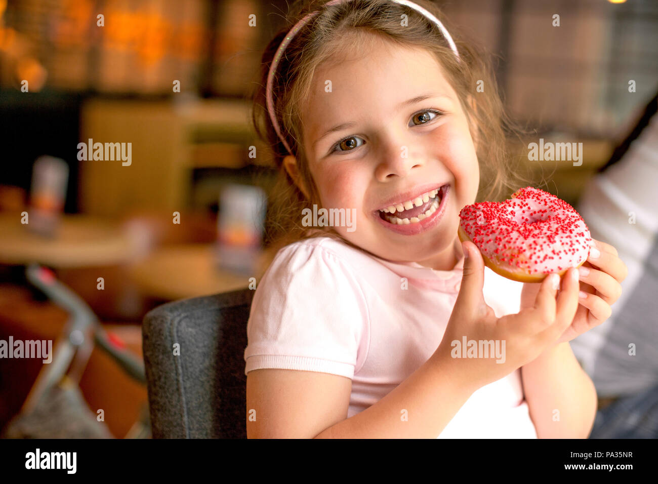 Niña feliz de comer en una cafetería y pastelería. Alimentos Dulces dañinos. Las tendencias en los alimentos. Espacio de copia Imagen De Stock