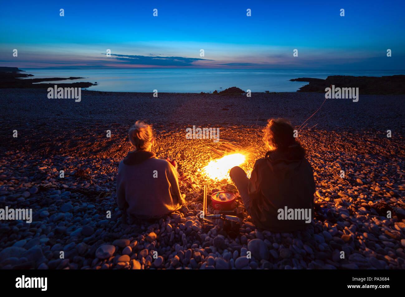 Un par de amigas sentados alrededor de un fuego de campamento en una playa de guijarros en la franja costera de Penmon popular punto en Anglesey contemplando el atardecer Imagen De Stock
