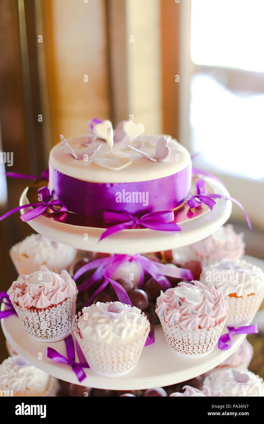 Decoraciones violeta y dulces deliciosos pasteles para fiesta. Imagen De Stock