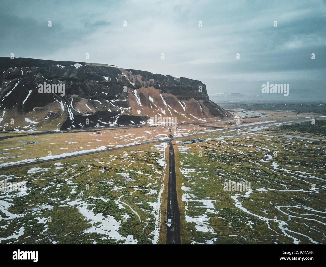 Fotografía aérea de montaña y carretera de circunvalación en Islandia con musgo verde y nieve Imagen De Stock