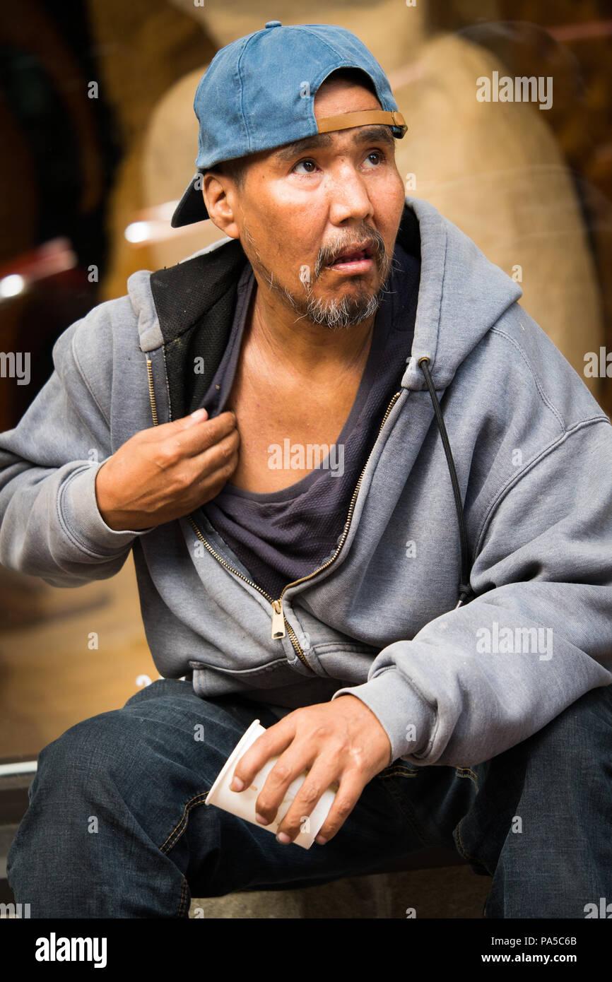 Native American hombre sentado en el banquillo en la acera usando luz azul sudadera con capucha gris Tapa de bola mirando a la esquina superior derecha rascarse el pecho. Imagen De Stock