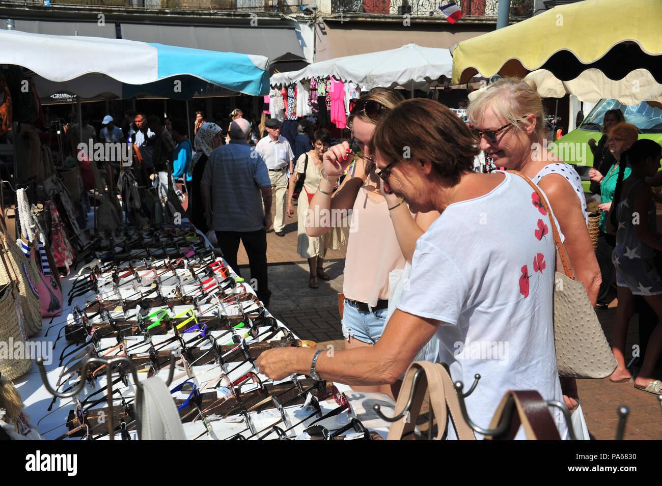 44ec6efb06 Un grupo de amigas de compras y tratando de gafas de sol en un puesto en