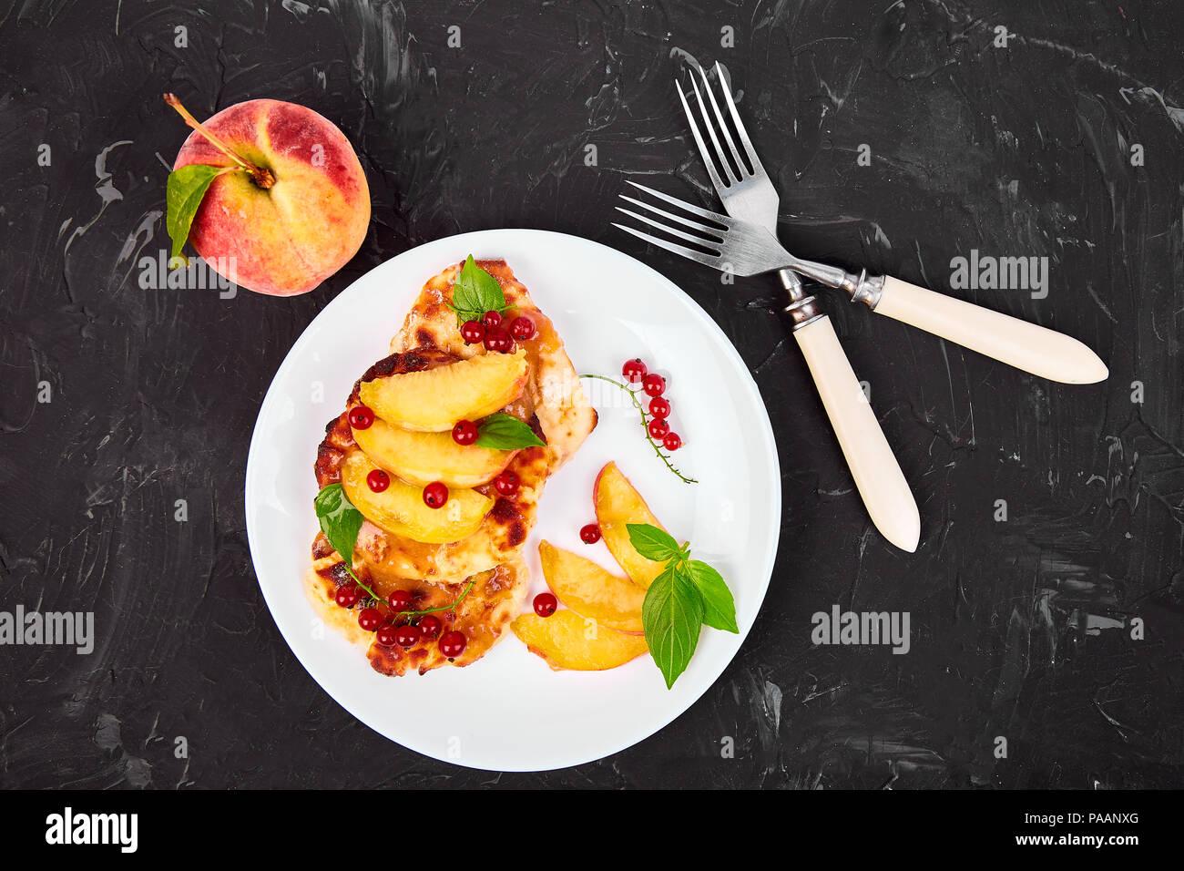 Requesón tortitas, syrniki con melocotón y bayas sobre placa blanca con fondo negro. Requesón buñuelos. Vista desde arriba. Sentar plana Foto de stock