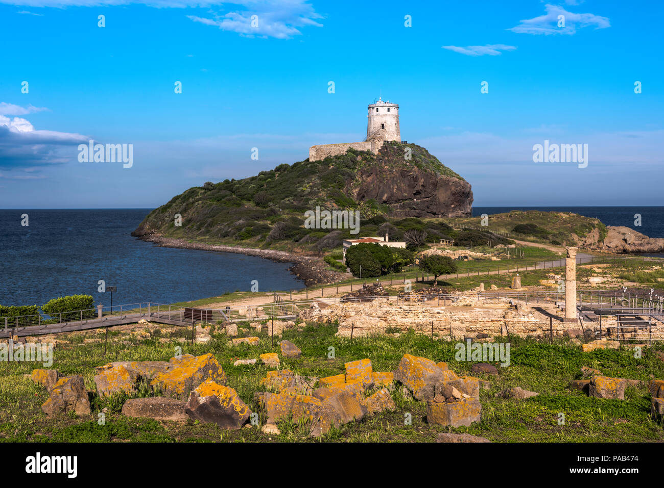Antigua torre sobre una colina en el mar Mediterráneo con las ruinas de Tharros delante (Cerdeña, Italia) Foto de stock