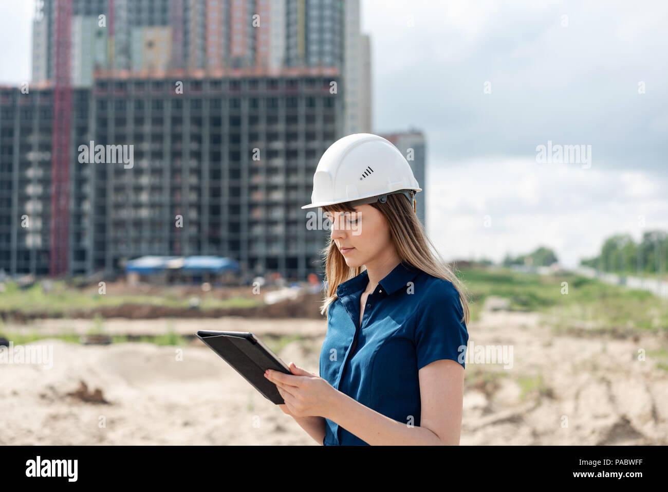 Ingeniero de la construcción femenina. Arquitecto con un equipo tablet PC en un sitio de construcción. Mujer joven busca, sitio de construcción lugar en segundo plano. Concepto de construcción Imagen De Stock