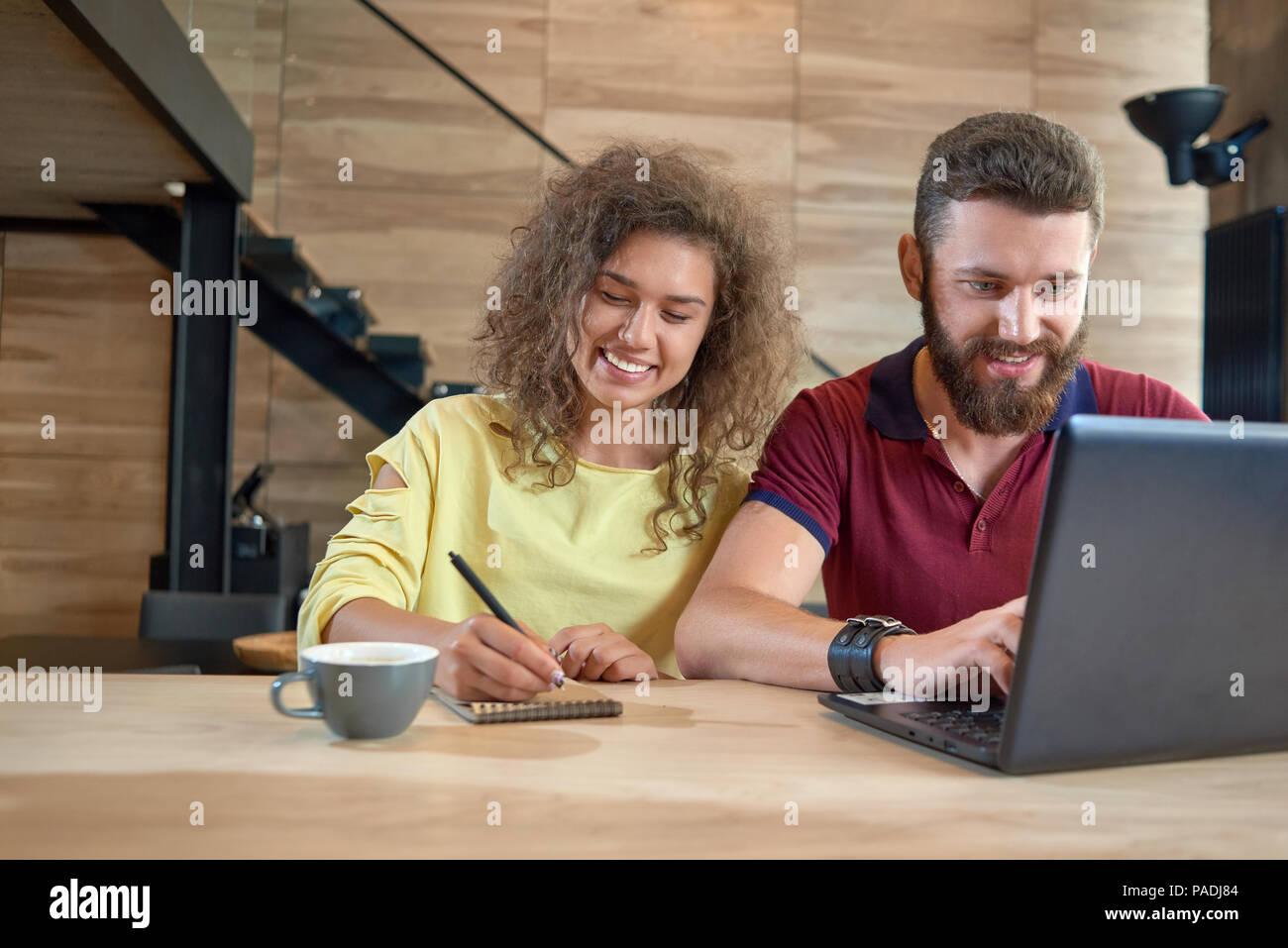 Estudio de estudiantes sentados en una cómoda cafetería, con laptop, sonriendo, riendo, bebiendo café estudiando, escribiendo notas. Posando sobre la mesa de madera con escaleras metálicas sobre fondo negro. Imagen De Stock