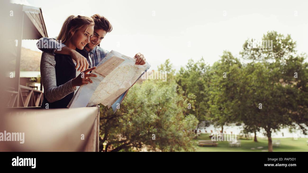 Par de pie fuera de su cabaña de vacaciones mirando el mapa para indicaciones. El hombre y la mujer de vacaciones buscando la ubicación en un mapa. Imagen De Stock