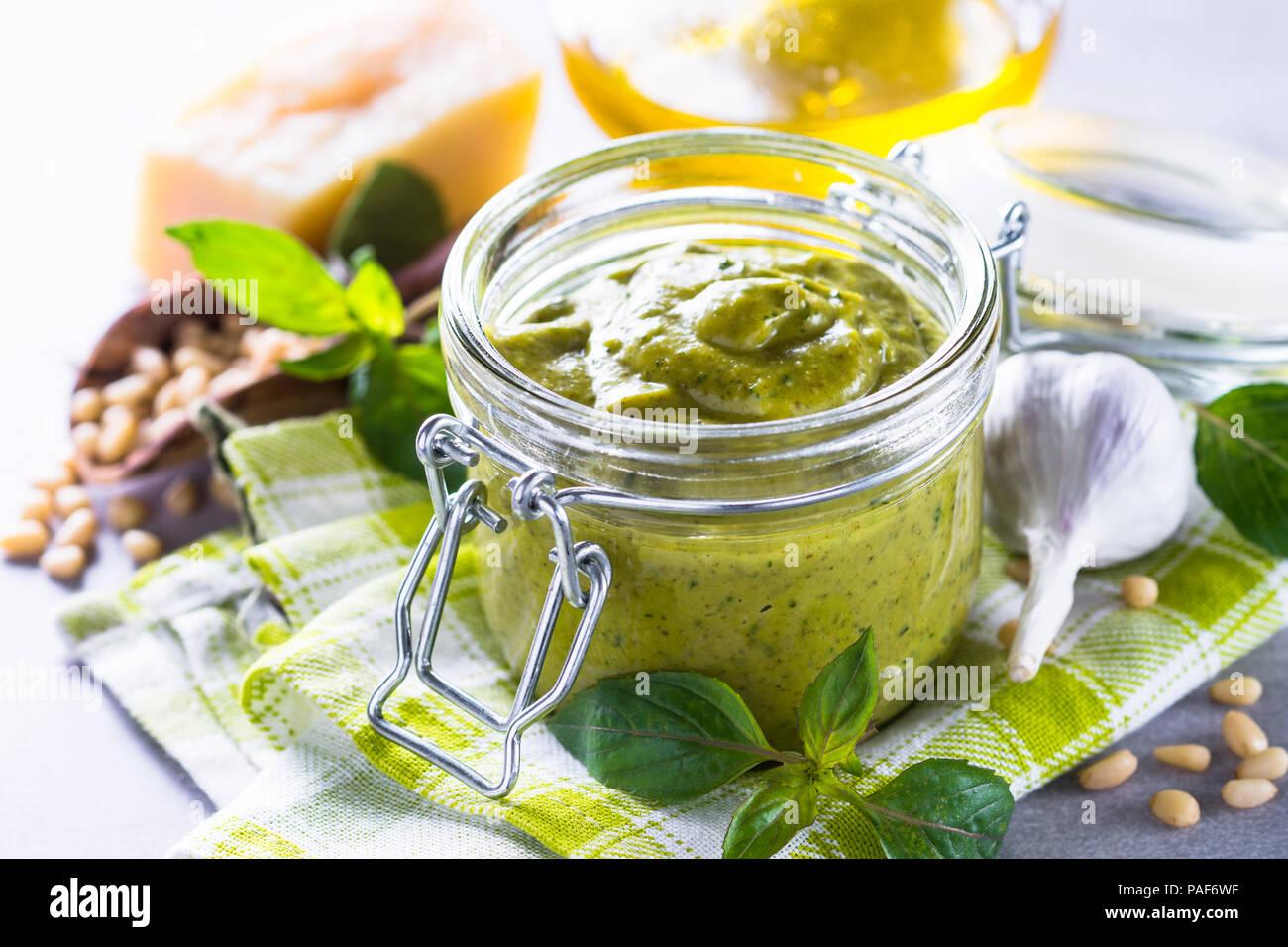 Salsa Pesto en frasco de vidrio y los ingredientes. Imagen De Stock