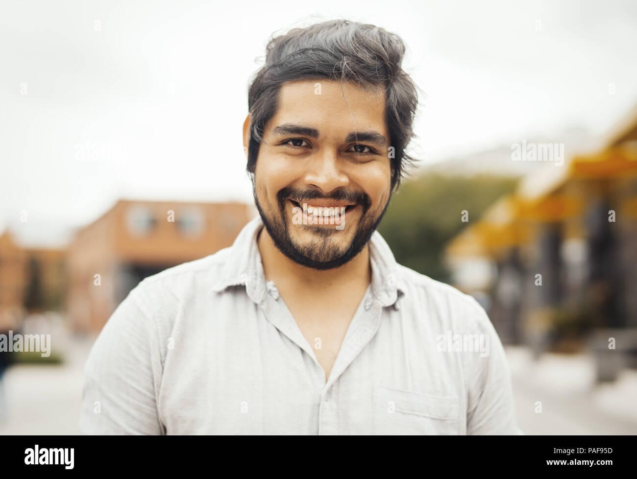 Atractiva morena América hombre mirando a la cámara y sonriendo. Imagen De Stock