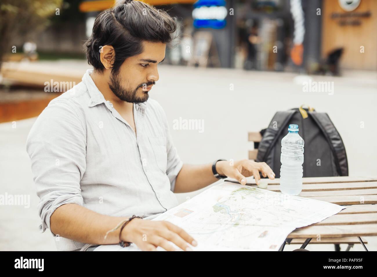 Hombre sentado en la cafetería de la calle y mirar el mapa. Junto al hombre es el agua embotellada. Imagen De Stock