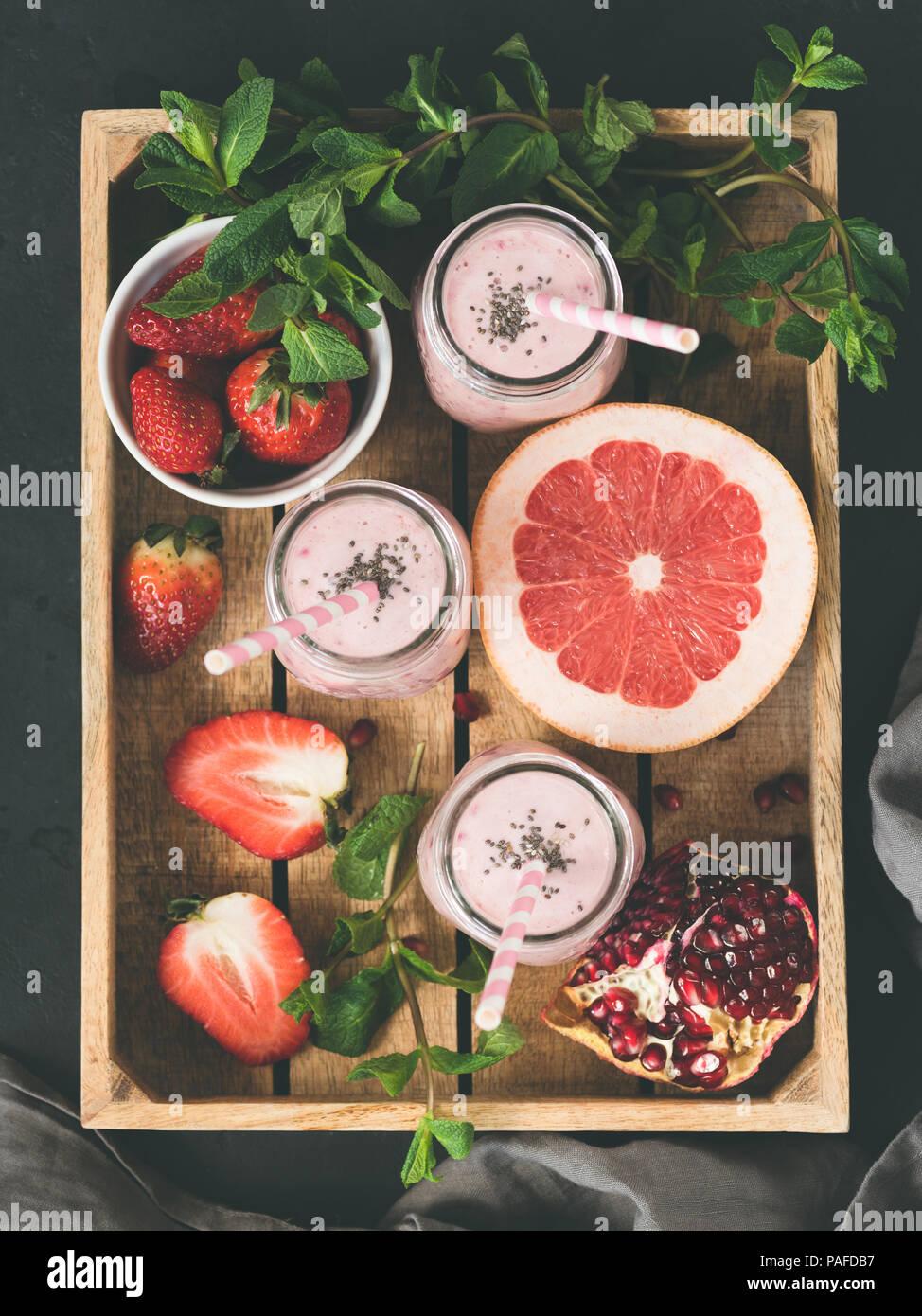 Los licuados de frutos y bayas en bandeja de madera, vista superior, imagen de tonos. Concepto de estilo de vida saludable y una alimentación saludable Imagen De Stock