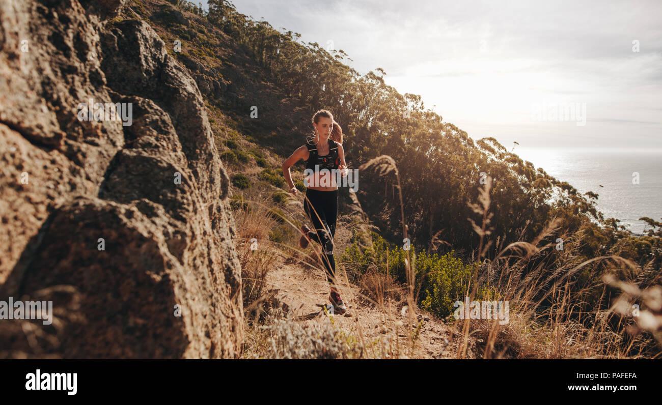 Mujer corriendo sobre terrenos extremos en la ladera de la colina. Corredoras formación afuera en Rocky Mountain trail. Imagen De Stock