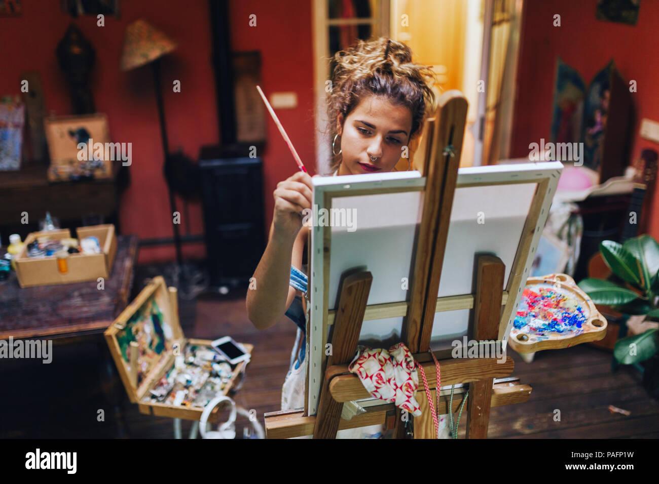 Filmación de interiores profesional de artista femenina de la pintura sobre lienzo en estudio con plantas. Imagen De Stock