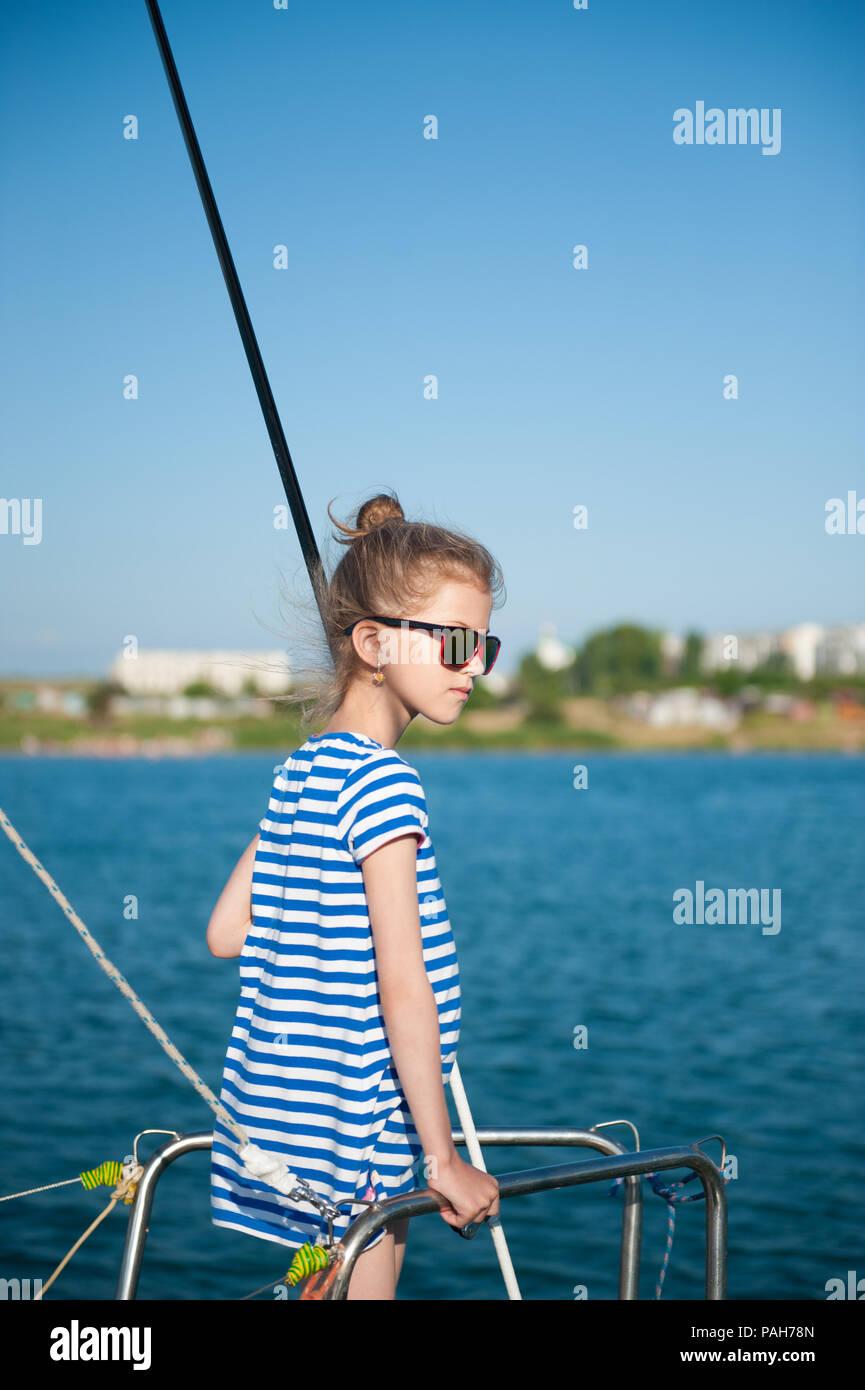 cc7e0f03bd Adorable niña en camisa a rayas y gafas de sol a bordo del yate de lujo