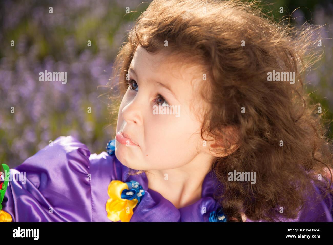 Cara graciosa mueca de linda chica con el pelo rizado en el exterior Imagen De Stock