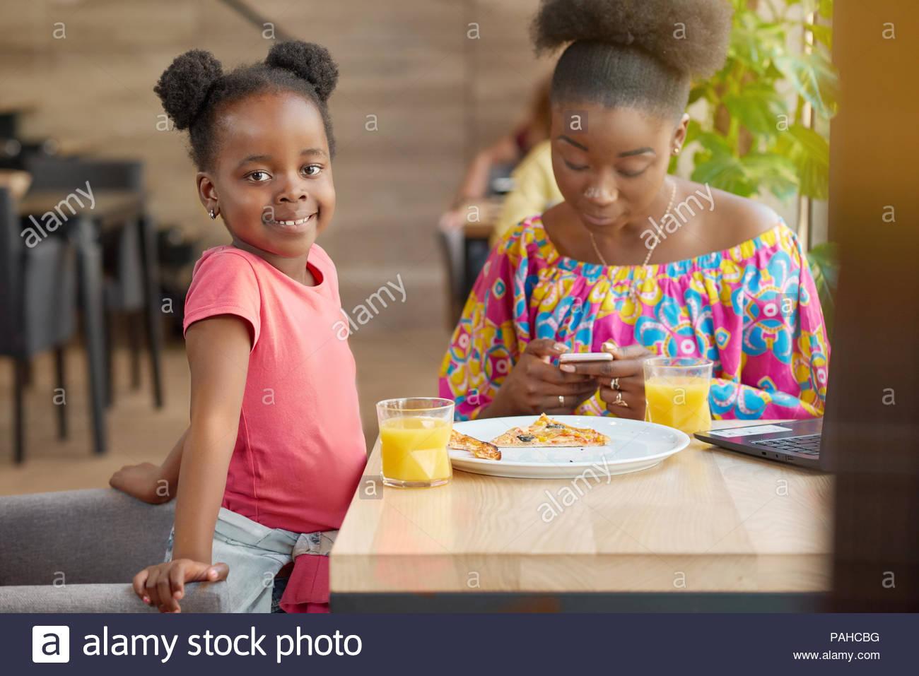 Sonriente, feliz, madre e hija beber zumo de naranja, comer pizza. Madre manteniendo smartphone, chatear en Internet. Cute Little Girl mirando a la cámara, sentirse feliz, pasar tiempo con la familia. Imagen De Stock