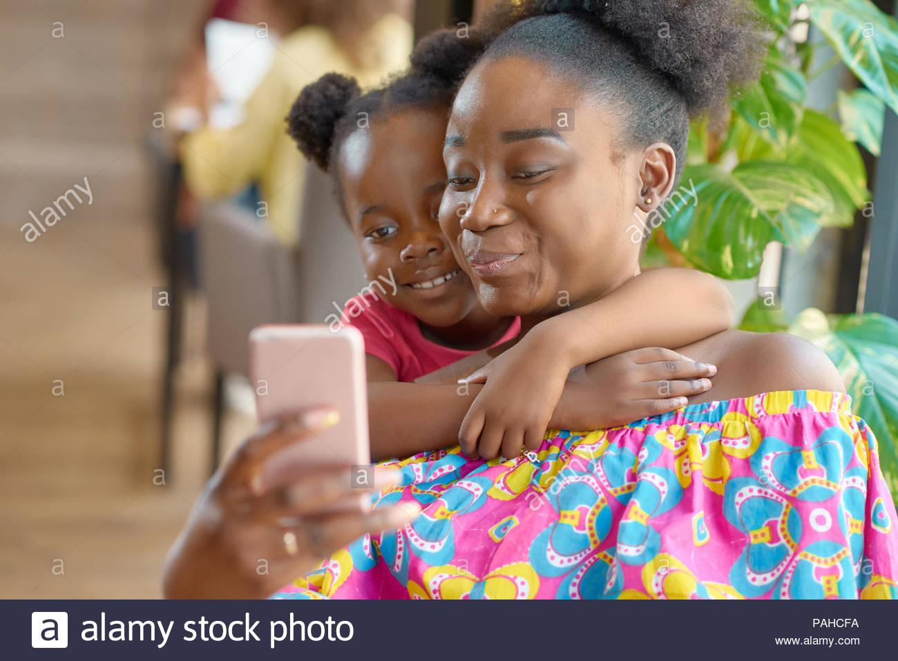 Teniendo selfie madre sonriente con su linda hija. Mirando el smartphone, sentirse feliz, satisfecho, relajado. Abrazos, preciosa foto de familia. Tener un buen tiempo. Sentado en la cafetería. Imagen De Stock