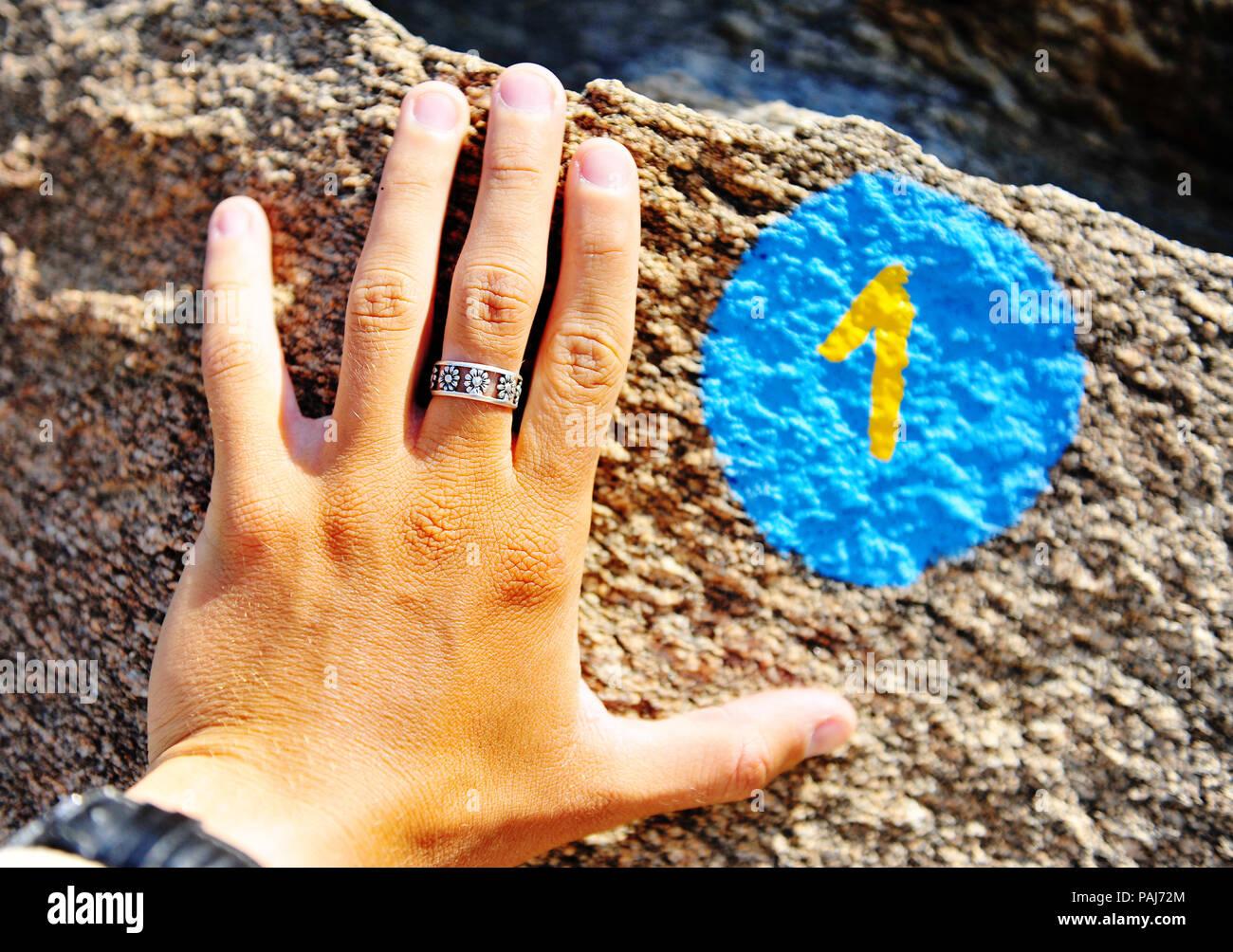 Mano con número 1 signo de trekking en piedra Imagen De Stock