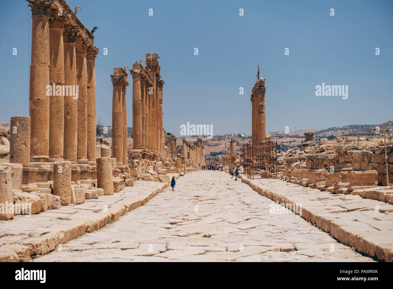 Antiguo grecorromano línea columnas calles adoquinadas en un cálido día de verano en Jerash, Jordania Foto de stock