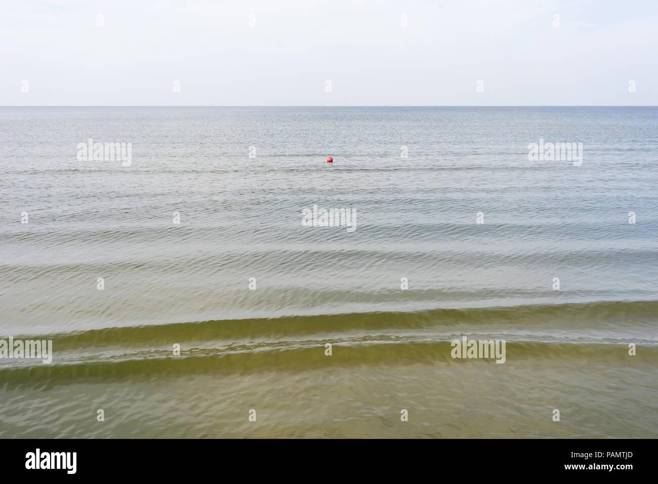 La boya roja flotando en el mar en calma clima con una sola ola sobre un fondo de cielo sin nubes Imagen De Stock