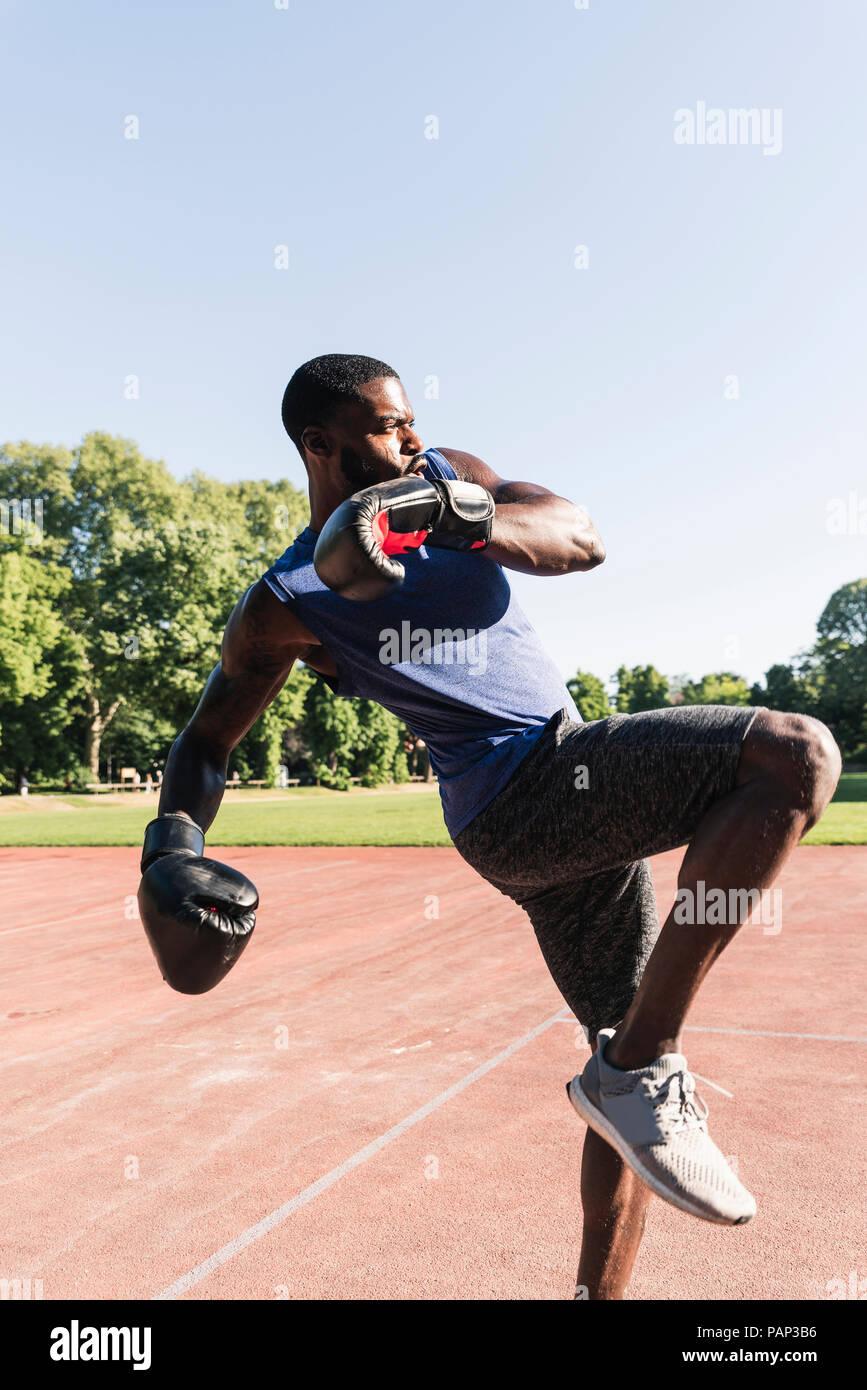 Joven hombre afroamericano boxeo entrenamiento en campo de deportes al aire libre Imagen De Stock
