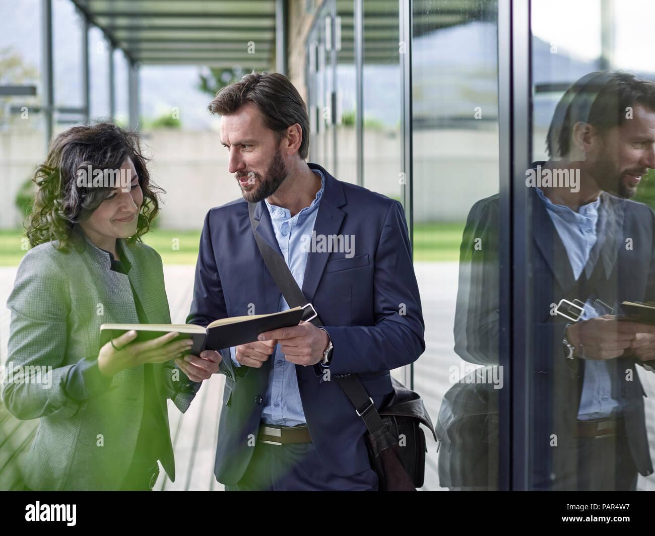 Los colegas con el libro hablando fuera de edificio de oficinas Imagen De Stock